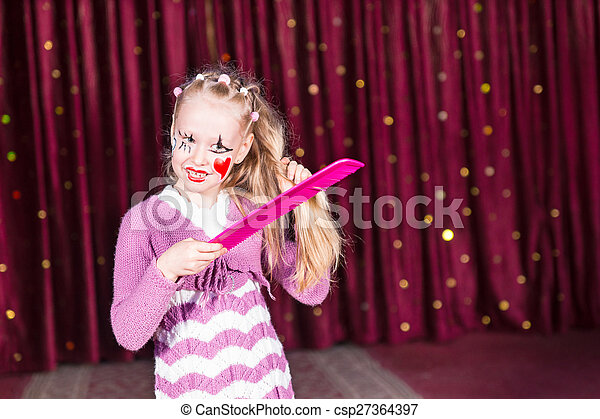 Pretty young girl in a pink pantomime costume - csp27364397