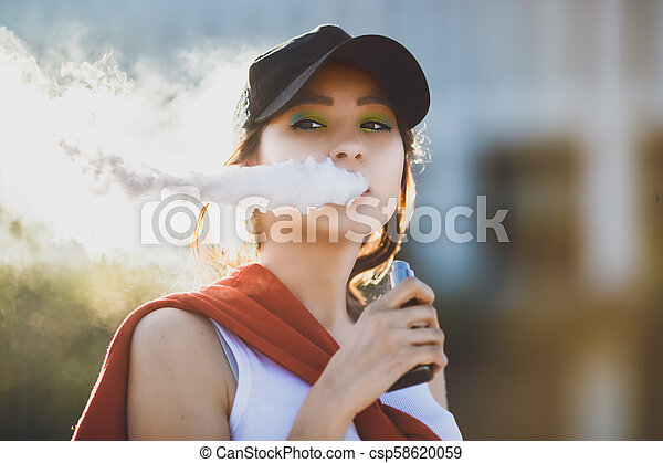 Pretty young hipster asian woman in black hat vape ecig, vaping device at the sunset. Toned image. Closeup. - csp58620059