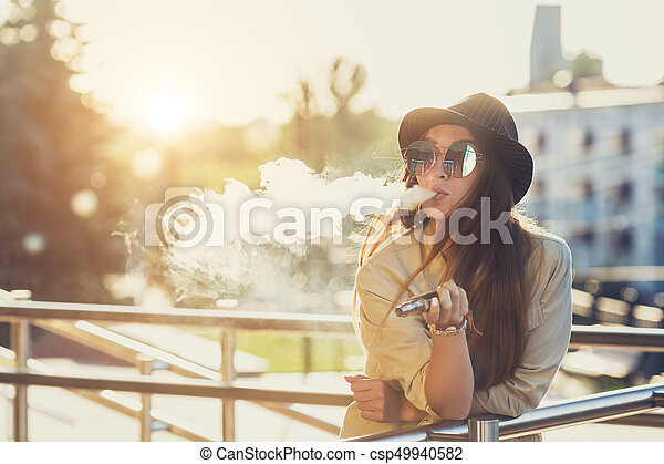 Pretty young hipster woman in black hat vape ecig, vaping device at the sunset. Toned image. - csp49940582