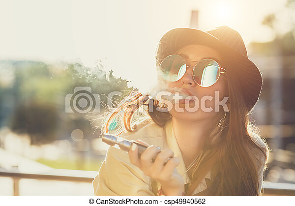 Pretty young hipster woman in black hat vape ecig, vaping device at the sunset. Toned image. - csp49940562