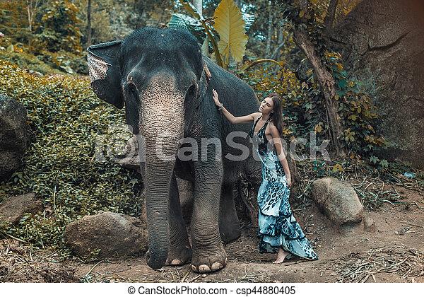 Pretty young lady cuddling an elephant - csp44880405