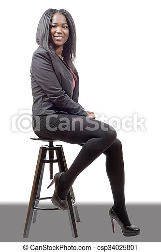 pretty young woman afro american businesswoman sitting on a stool - csp34025801