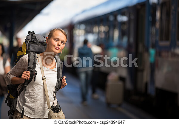 Pretty young woman boarding a train - csp24394647