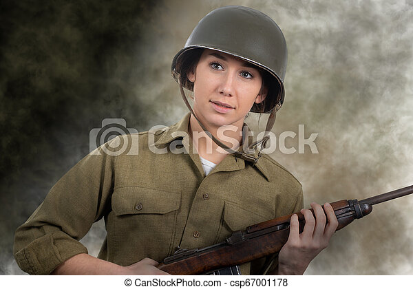 pretty young woman dressed in wwii american military uniform with helmet  and rifle
