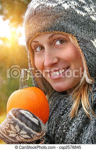 Pretty young woman holding a pumpkin - csp2576845