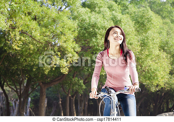 Pretty young woman riding bike in the park - csp17814411