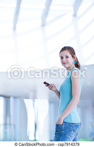 Pretty, young woman using her mobile phone/speaking on the phone in a public area (shallow DOF; color toned image) - csp7914379