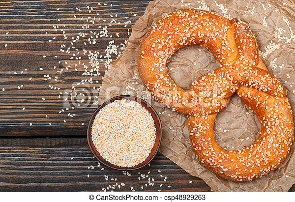 Pretzel with sesame seeds on the dark wooden table. Selective focus. Copy space. Top view - csp48929263