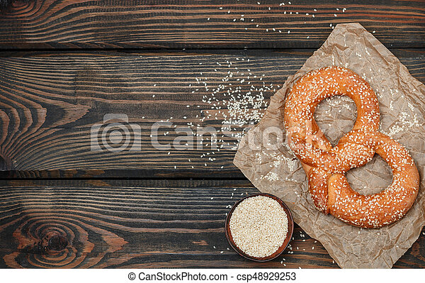 Pretzel with sesame seeds on the dark wooden table. Selective focus. Copy space. Top view - csp48929253
