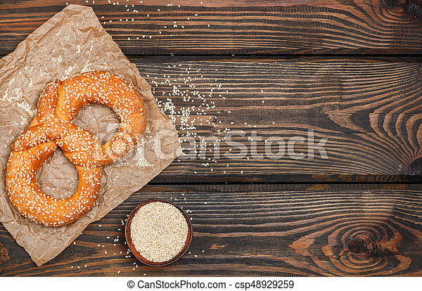 Pretzel with sesame seeds on the dark wooden table. Selective focus. Copy space. Top view - csp48929259