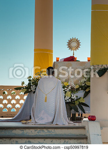 Priest Kneel Down in front of an Altar: Outdoor Church - csp50997819