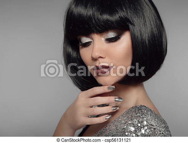 Maquillaje y uñas pintadas. Una chica a la moda peinado negro Bob. Retrato de moda de Brunette Estilo Mujer Retrato con pelo negro y labios brillantes aislados en el fondo gris. - csp56131121