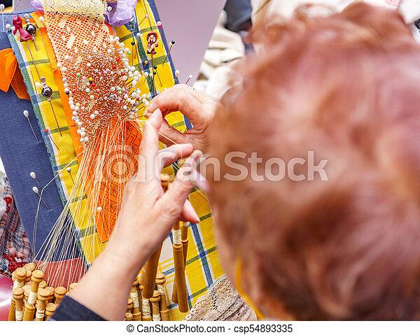 Un primer plano de una anciana que trabaja en encajes - csp54893335