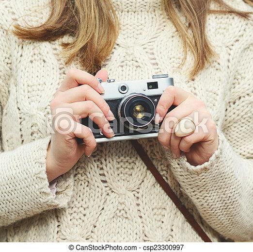 Una mujer sosteniendo un primer plano de cámara retro - csp23300997