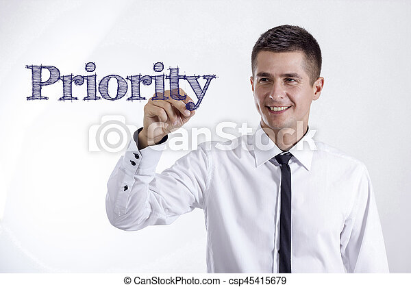 Priority - Young smiling businessman writing on transparent surface - csp45415679