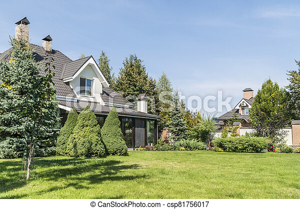 private house with its beautiful garden in a rural area under blue sky - csp81756017