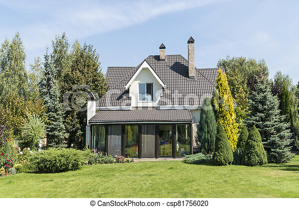 private house with its beautiful garden in a rural area under blue sky - csp81756020