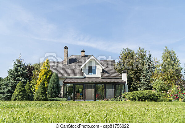 private house with its beautiful garden in a rural area under blue sky - csp81756022
