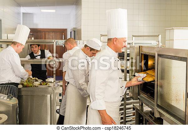 Grupo de cocineros en la cocina profesional - csp18246745
