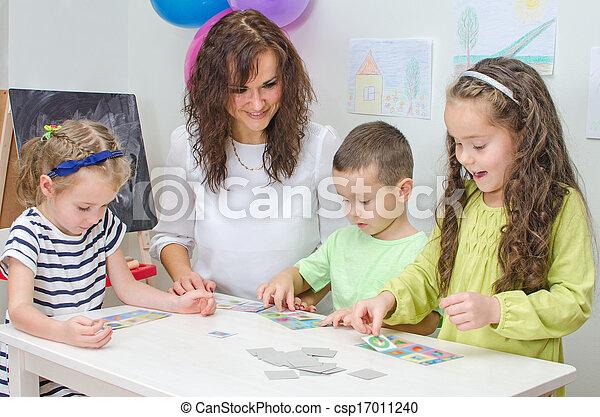 El maestro juega con niños en la guardería. - csp17011240