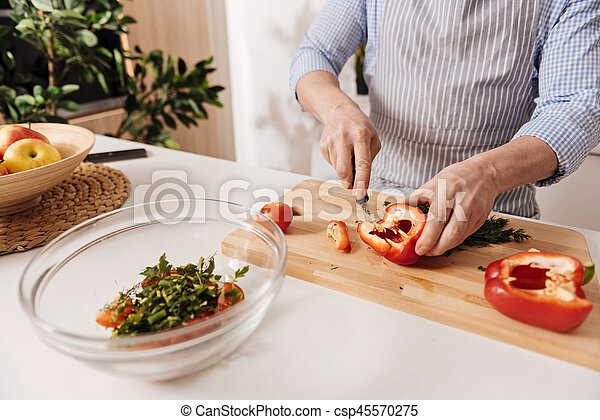 Professional cook cutting pepper for dinner in the kitchen - csp45570275