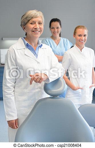 Professional dentist team woman at dental surgery - csp21008404