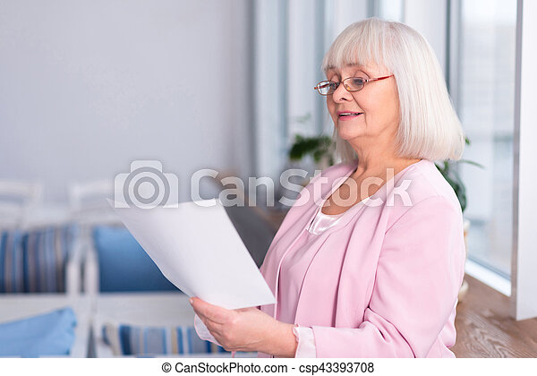 Professional elderly woman reading a document - csp43393708