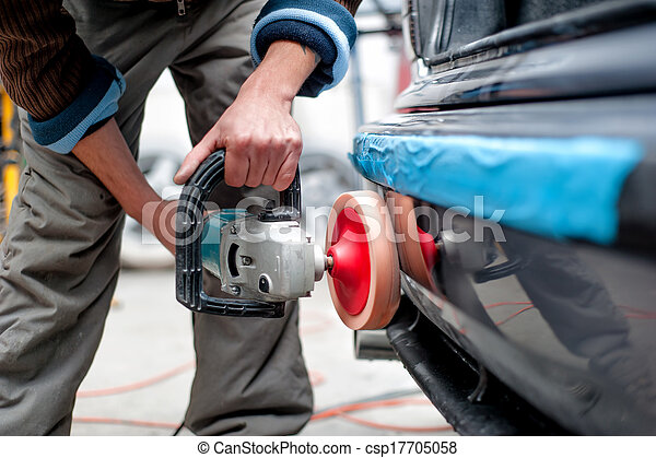 professional mechanic using a power buffer machine for cleaning the body of a car from scratches. Detail of car care concept - csp17705058