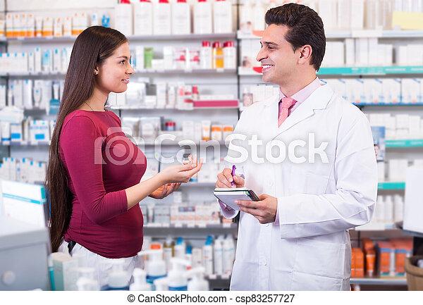 Professional pharmaceutist in drugstore helping girl - csp83257727