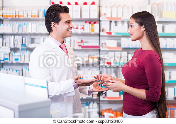 Professional pharmaceutist in drugstore helping girl - csp83128400