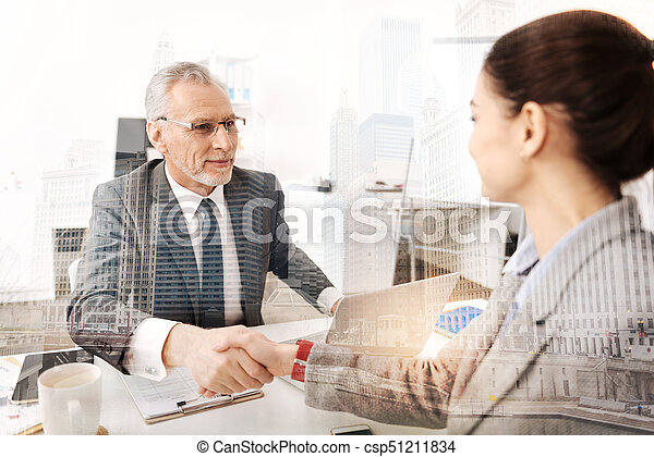 Professional smiling boss having a firm handshake with a new female colleague - csp51211834
