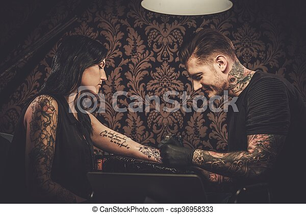 b2f351afa Professional tattoo artist makes a tattoo on a young girl's hand.