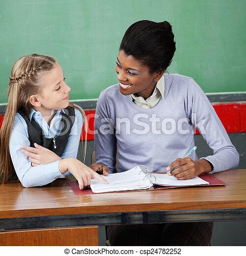 Professor Looking At Schoolgirl At Desk - csp24782252