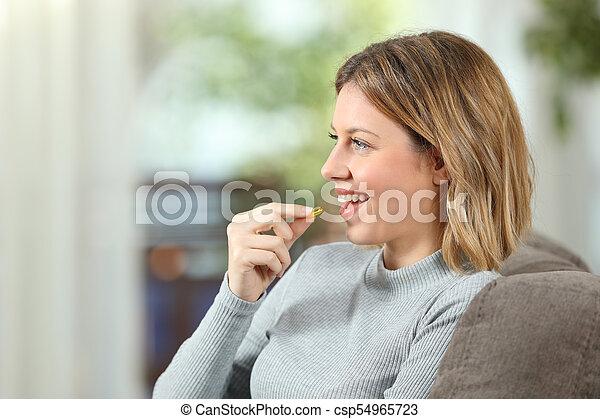 Profile of a happy woman taking a vitamin pill - csp54965723
