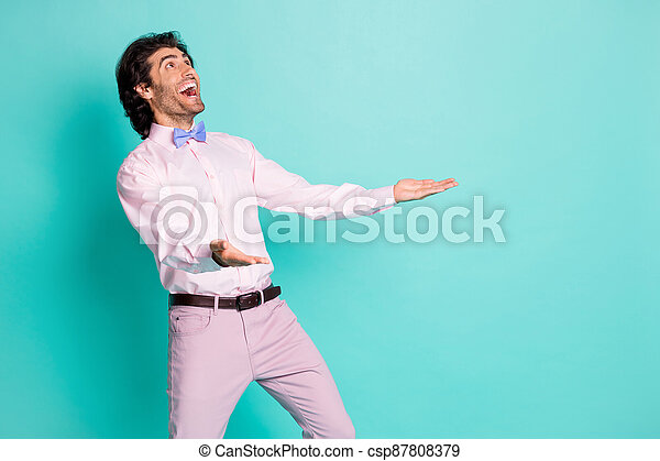 Profile photo of cute funny boyfriend wear pink outfit looking up empty space arms up open mouth isolated teal color background - csp87808379