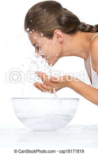 Profile portrait of young woman washing face in glass bowl with water - csp18171819