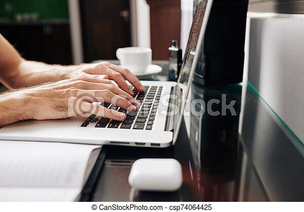 Programming student working on laptop - csp74064425