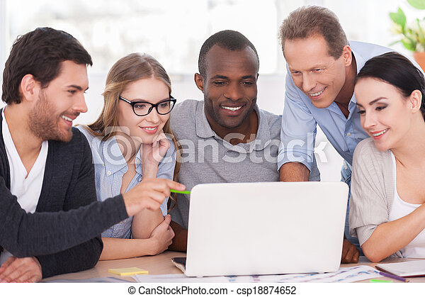 Equipo creativo trabajando en proyecto. Un grupo de empresarios con ropa informal sentados juntos en la mesa y mirando el portátil - csp18874652