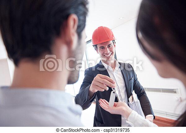 Una pareja comprando una nueva casa con un agente inmobiliario - csp31319735