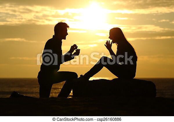 Proposal on the beach with a man asking for marry at sunset - csp26160886