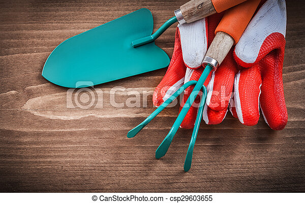 Protective gloves trowel and rake on wooden board - csp29603655