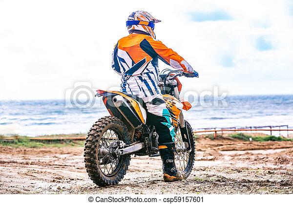 Un motociclista con un traje protector sentado en moto frente al mar - csp59157601