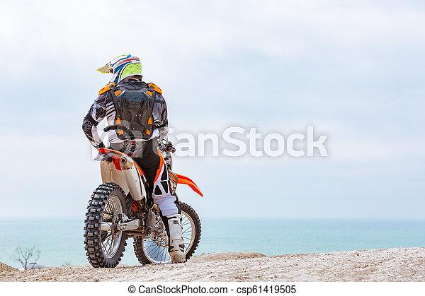 Un motociclista con un traje protector sentado en moto frente al mar - csp61419505