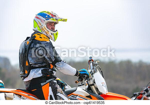 Un motociclista con un traje protector sentado en moto frente al mar - csp61419535
