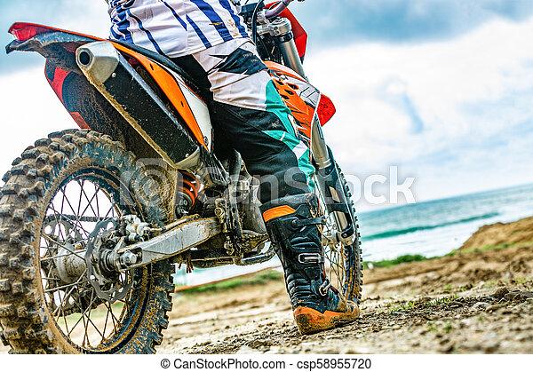 Un motociclista con un traje protector sentado en moto frente al mar - csp58955720