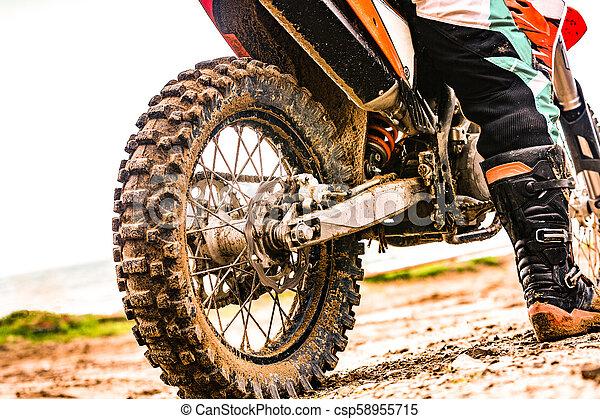 Un motociclista con un traje protector sentado en moto frente al mar - csp58955715