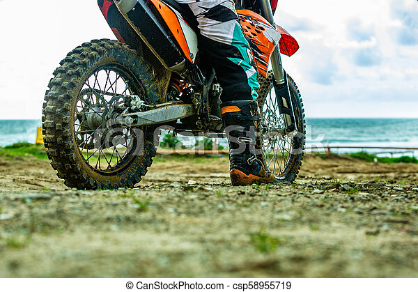 Un motociclista con un traje protector sentado en moto frente al mar - csp58955719
