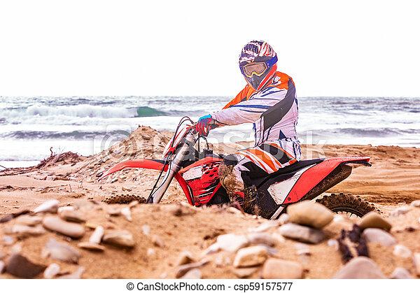 Un motociclista con un traje protector sentado en moto frente al mar - csp59157577