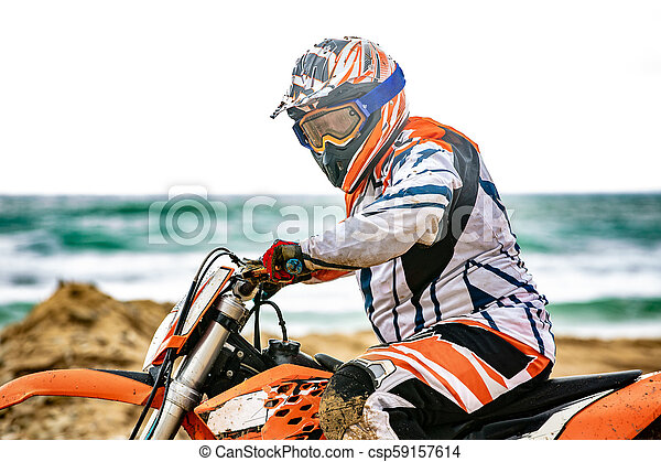 Un motociclista con un traje protector sentado en moto frente al mar - csp59157614