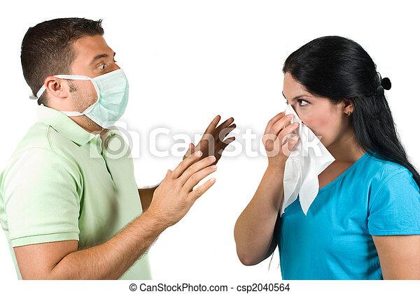 Un hombre aterrorizado con máscara protector trata de detener a una mujer estornudante - csp2040564